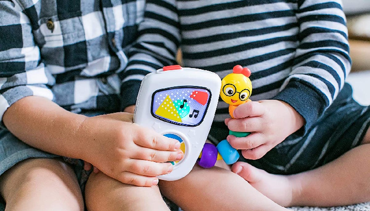 Two toddlers sitting on a rug hold a musical toy.