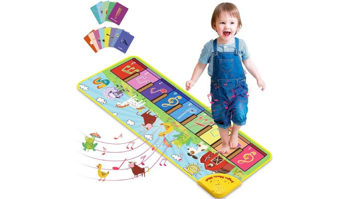 A toddler in blue jean overalls plays a colorful musical mat.
