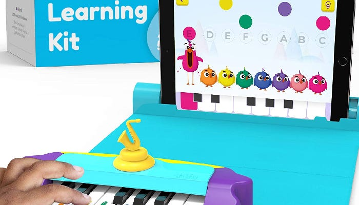 A toddler's fingers are shown playing a small, purple toy keyboard that is connected to a tablet in the background.