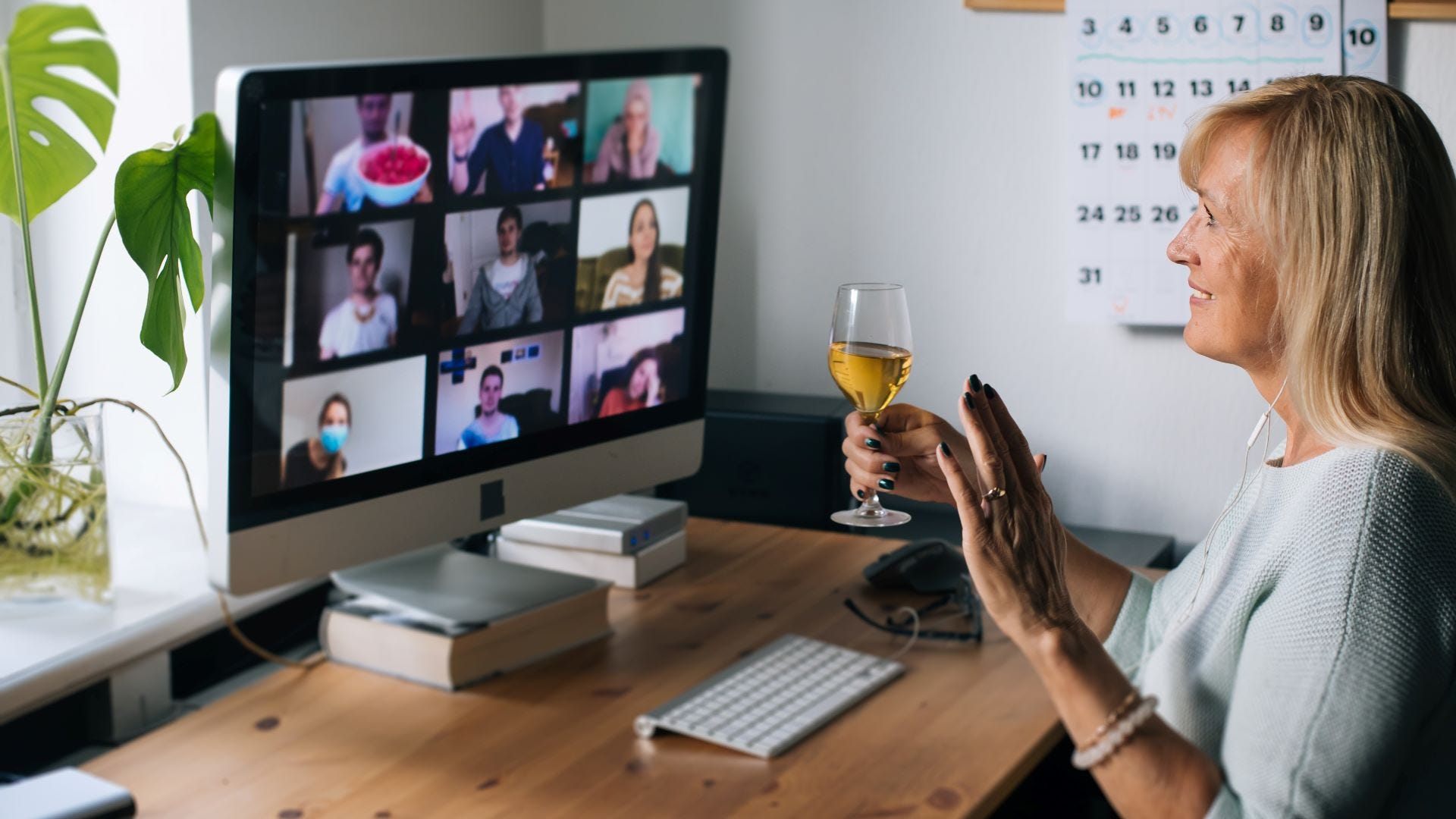 A woman holding a glass of wine while chatting with friends during a Zoom Call.