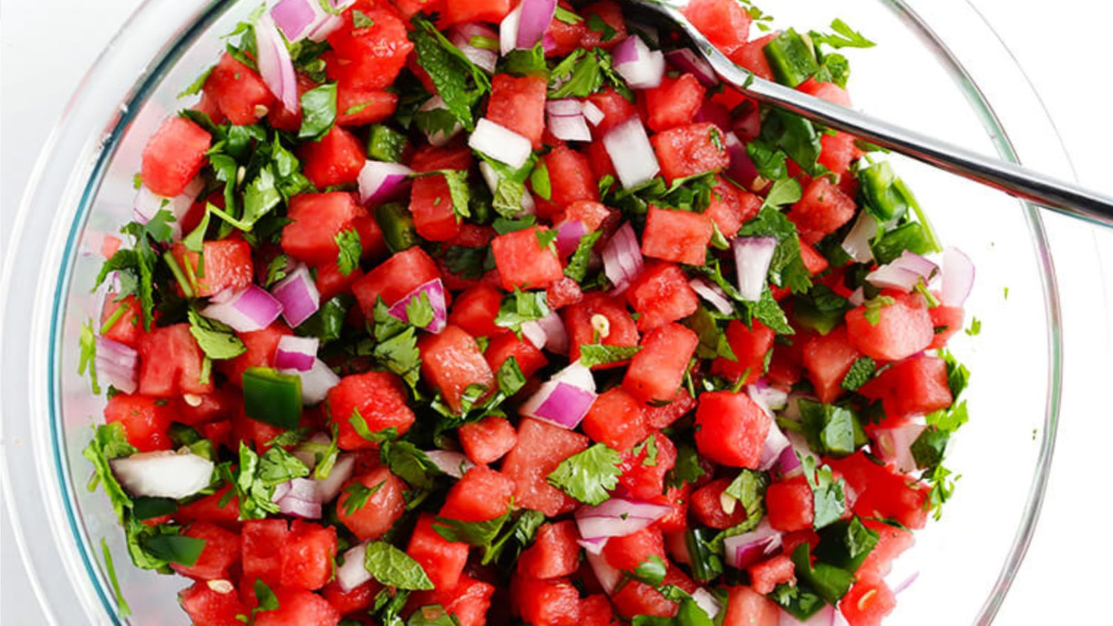 A glass bowl full of watermelon salsa made with diced watermelon, red onion, mint, cilantro and jalapeno.