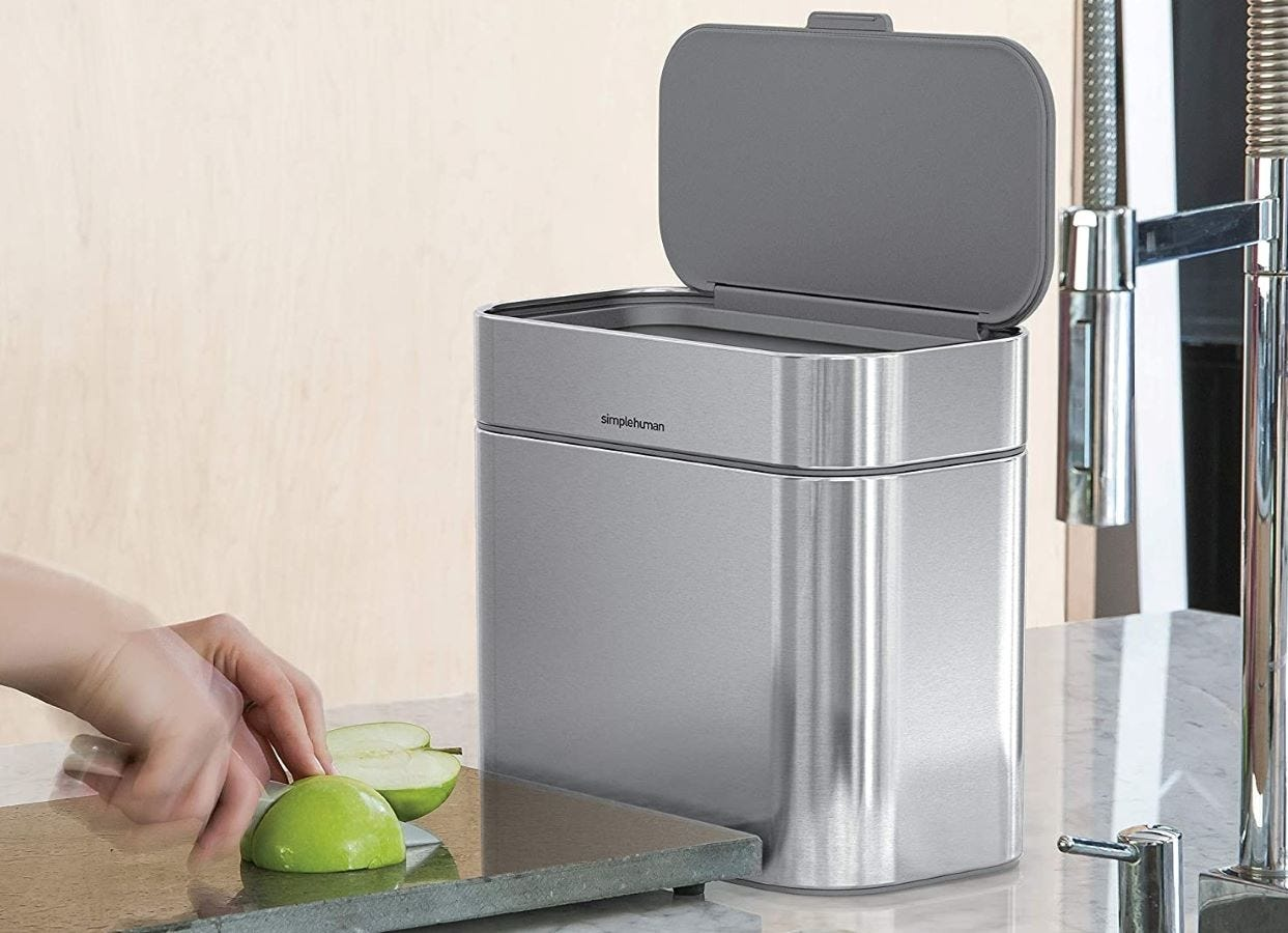 Someone slicing an apple on a cutting board next to the simplehuman Compost Caddy.