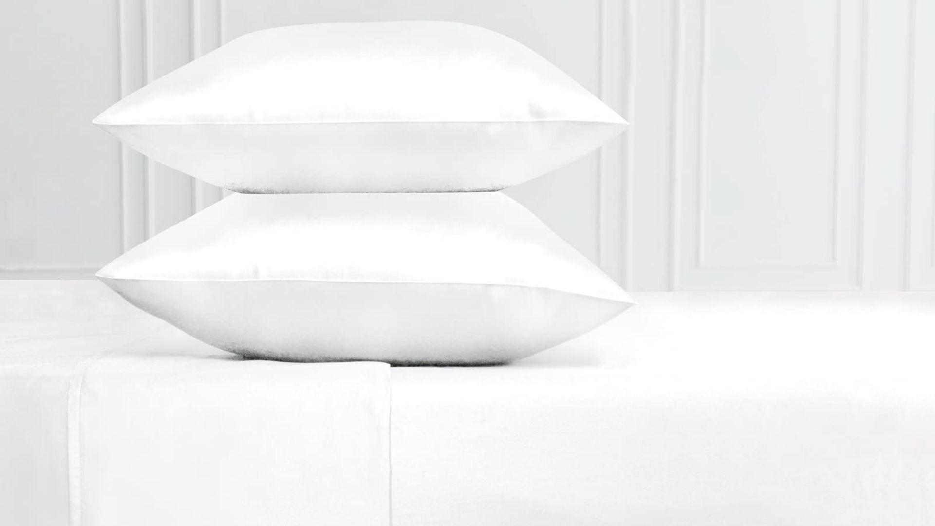 Две белые подушки сложены на кровати с новыми белыми хлопковыми простынями.