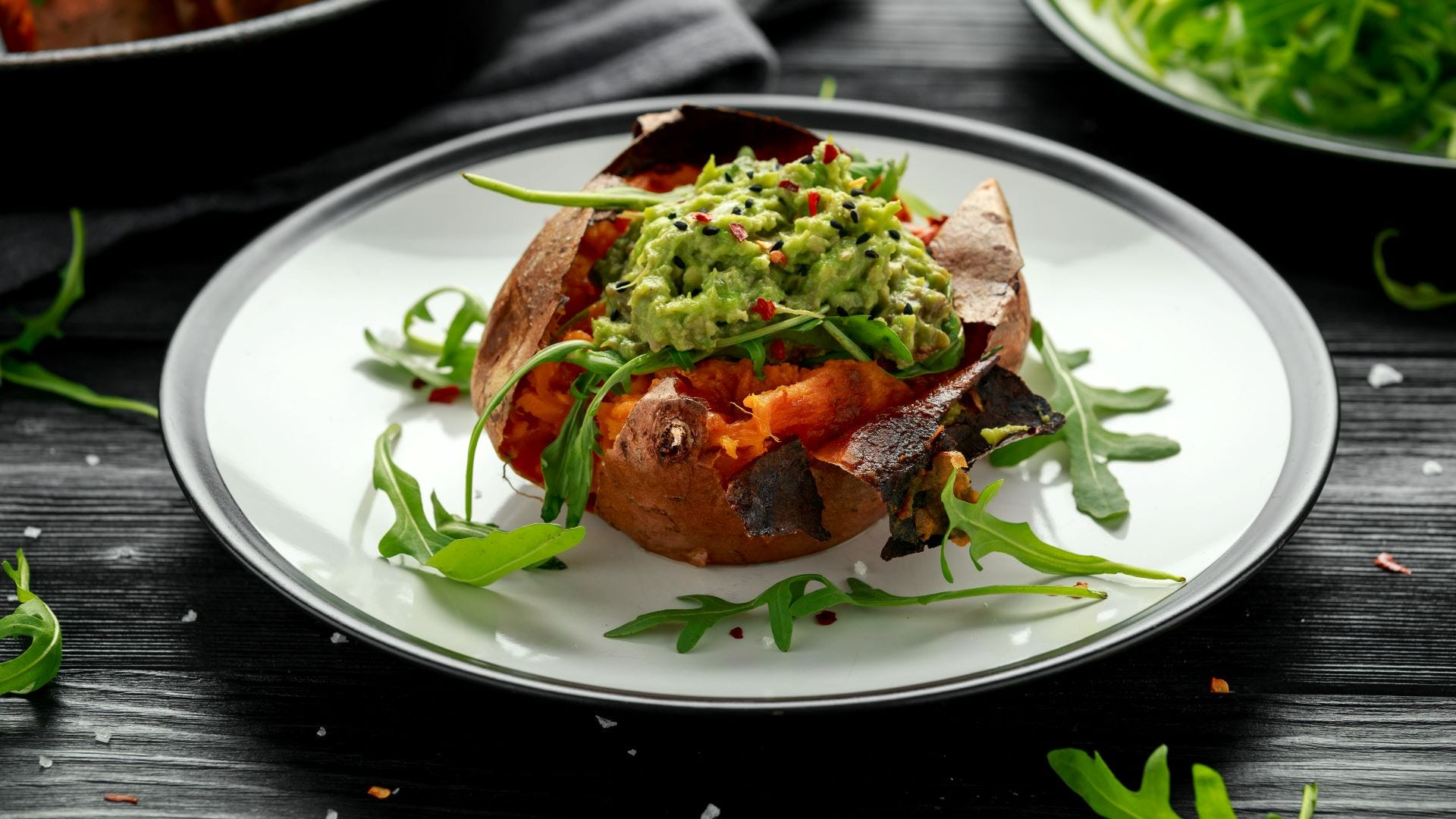 A sweet potato boat stuffed with avocado guacamole and wild rocket sprinkled with nigella seeds.