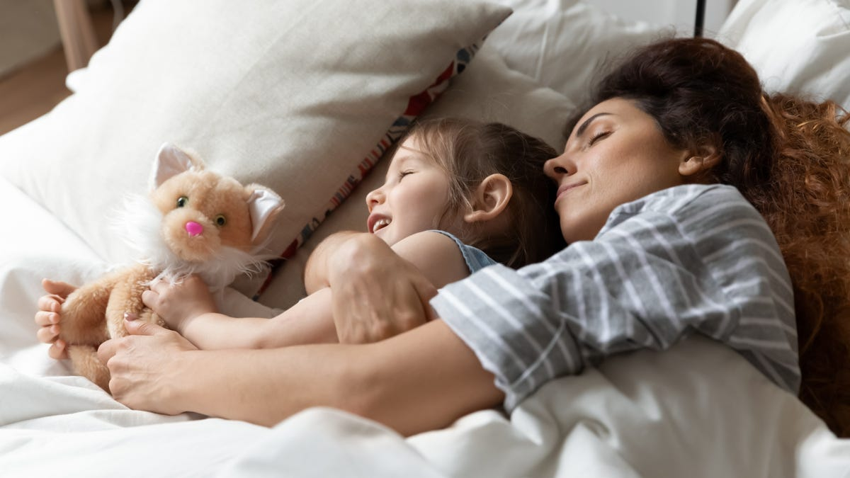 Serene girl holds a cat stuffed animal toy as her mother holds her.