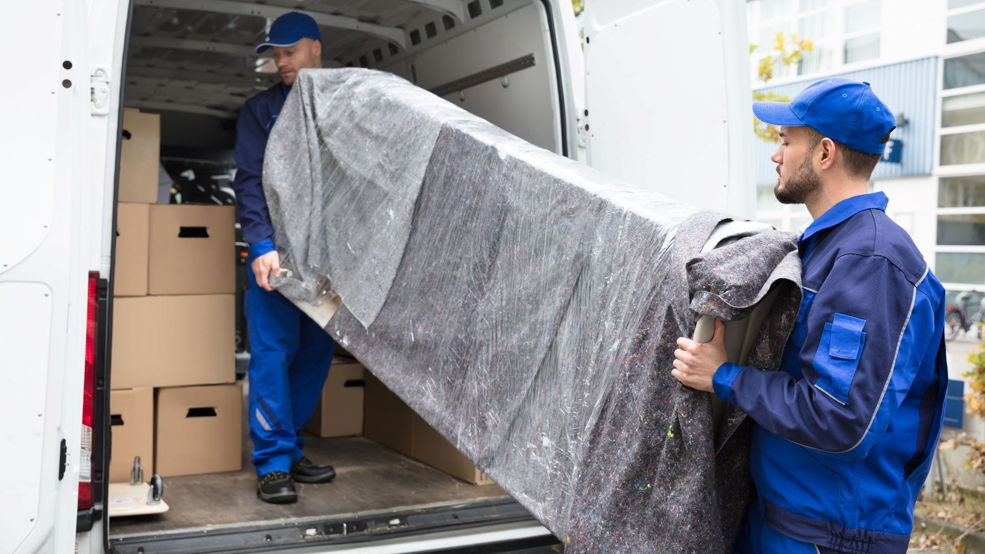 Two movers loading a piece of furniture on a moving truck.