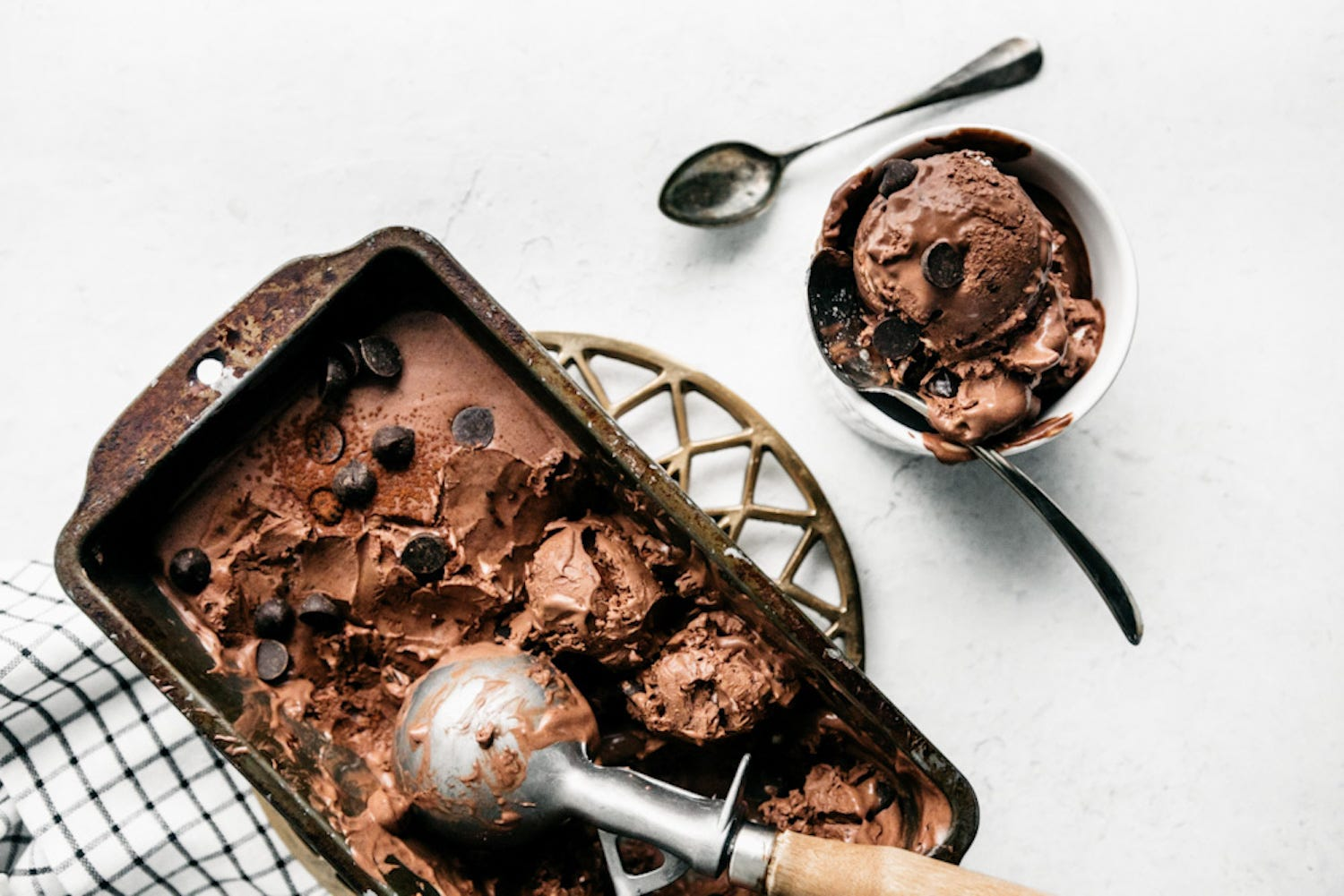 A tray of chocolate chip ice cream with a scoop in it, with a bowl of ice cream next to it