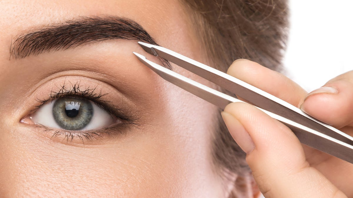 close-up of a woman using silver tweezers on her eyebrow