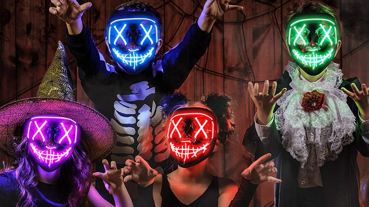 Four kids wearing Halloween costumes and colorful LED masks.