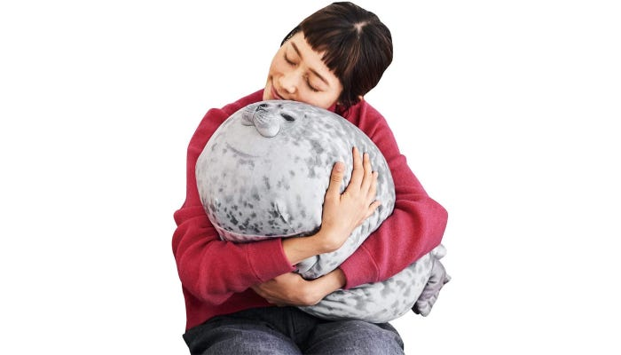 A woman hugs a wide, 23.6-inch seal that features a white and gray speckled pattern.