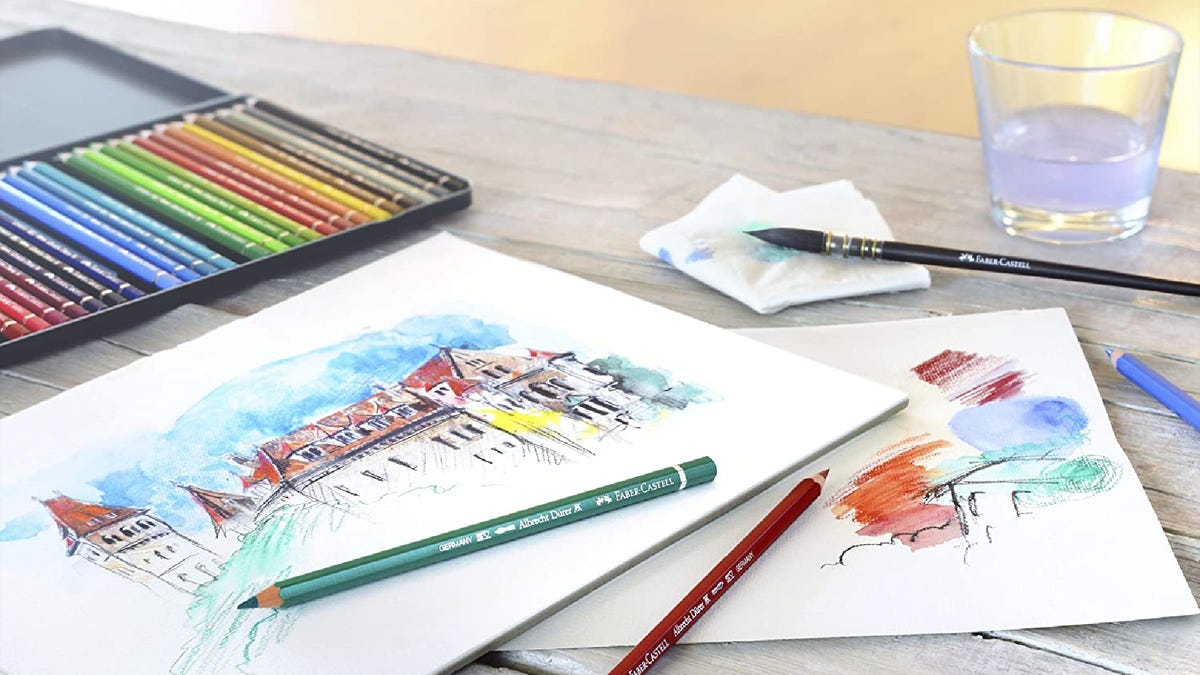 a drawing of an old building set on a hill with watercolor pencils, a glass of water, and a paintbrush closeby