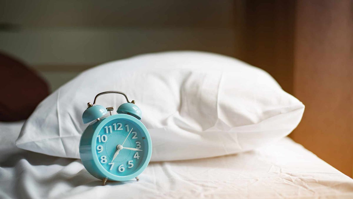 An old fashioned alarm clock sitting on a bed next to a pillow as the early morning sun streams in the window.