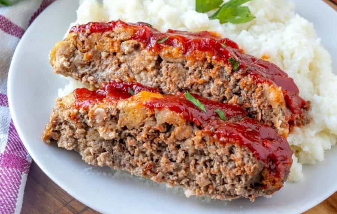Two slices of meatloaf on a plate with mashed potatoes.