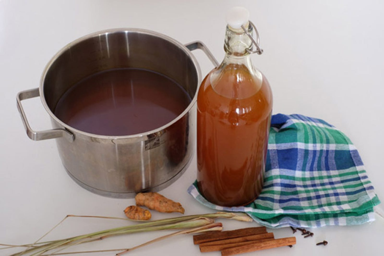 A big pot with tamarind juice next to a bottle with the same drink, standing over a blue checkered tablecloth, with bits of ginger, lemongrass, and cinnamon sticks next to it.