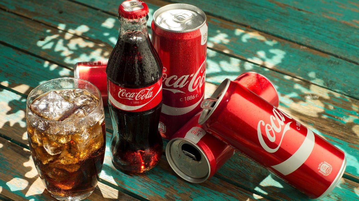 A bottle and four cans of Coca-Cola on a table next to a glass filled with it and some ice.