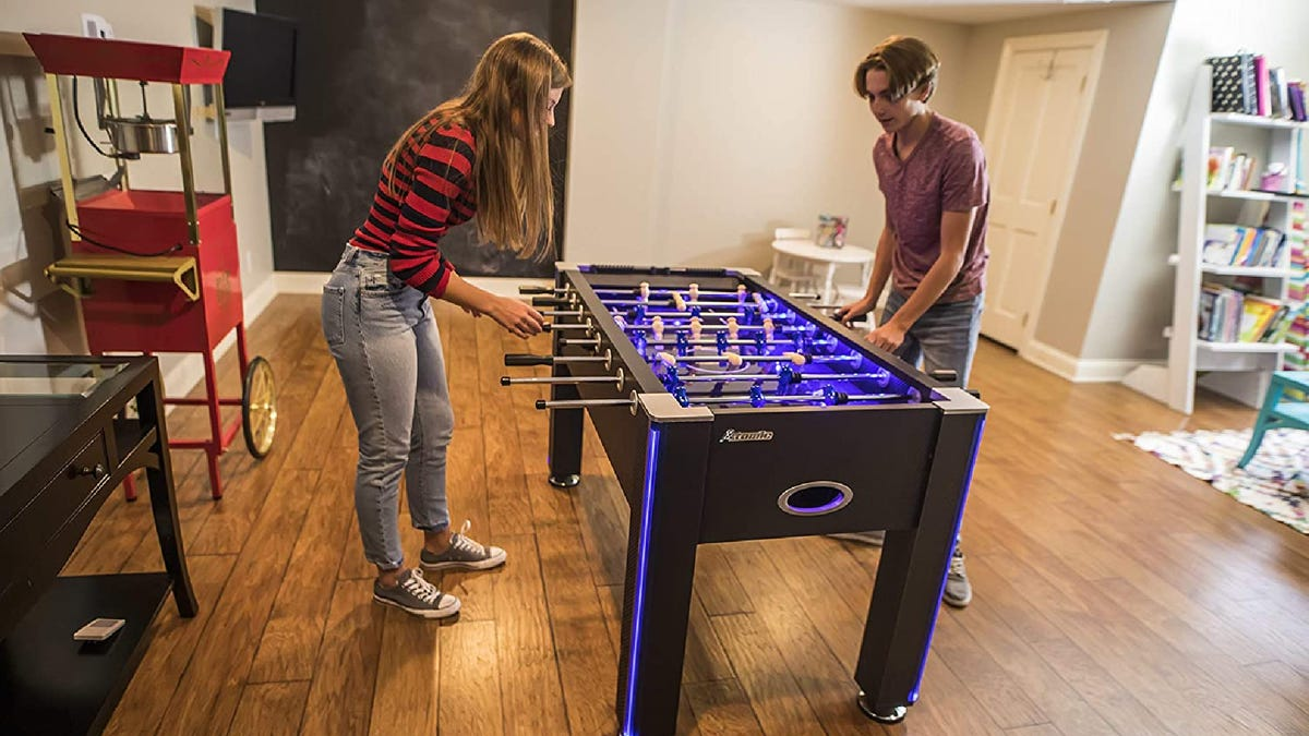 two teenagers playing foosball on a light-up foosball table in a game room of a hom