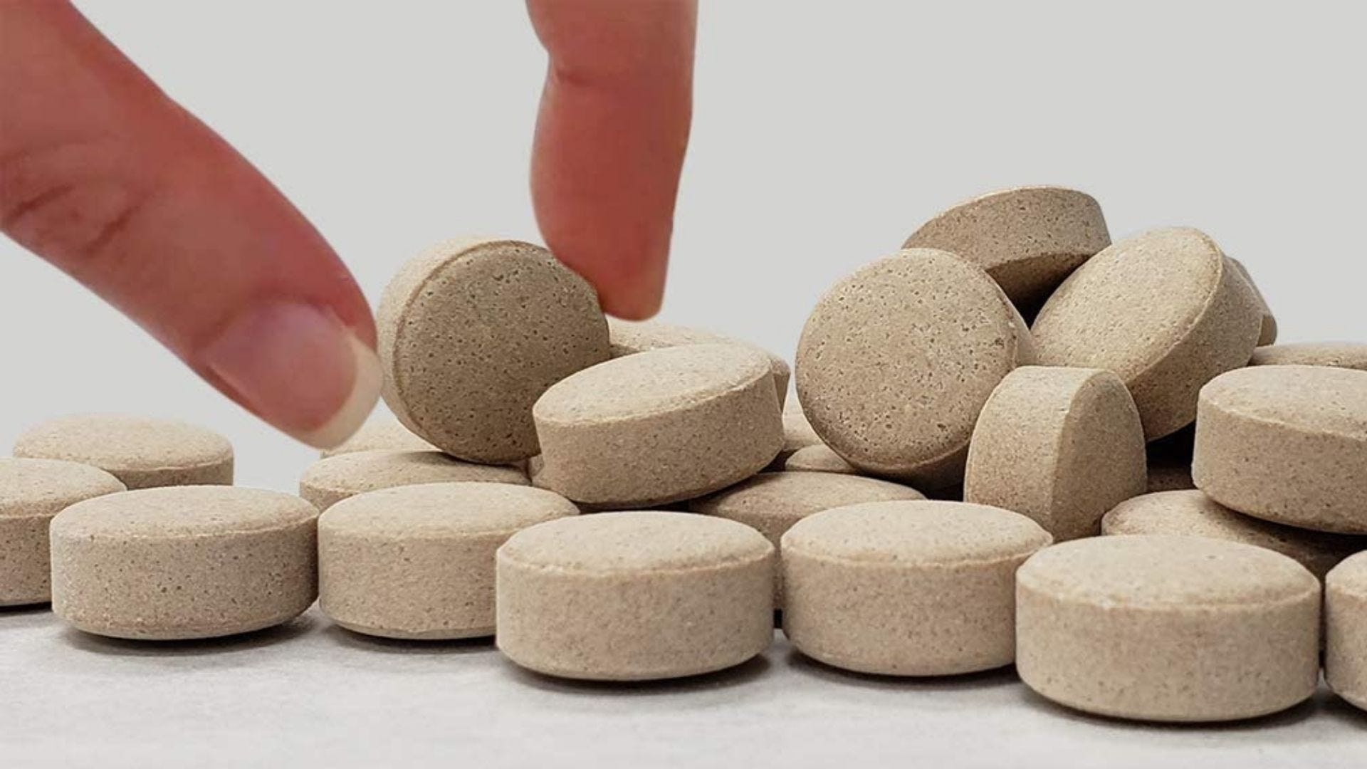 Someone picks up a beige-colored vitamin tablet