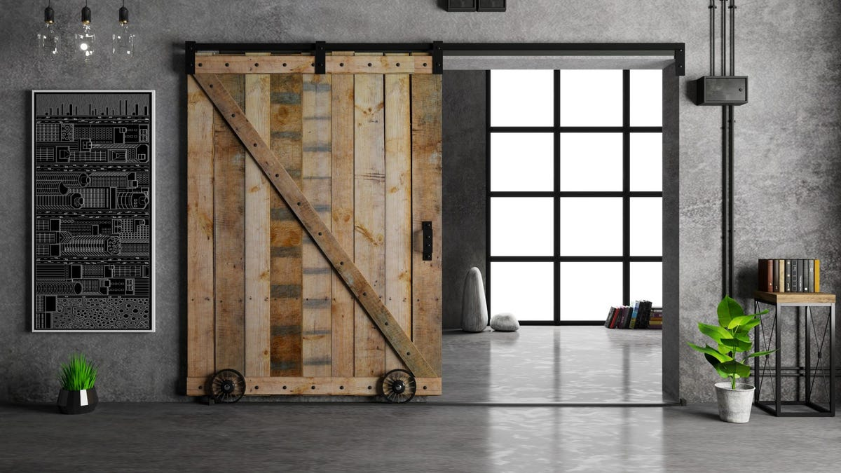 A rustic barn door in a stylish home with gray, marble-look walls.