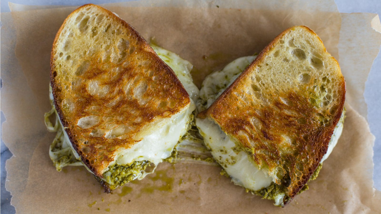 A pesto grilled cheese sandwich made with sourdough bread, sitting on a piece of parchment.
