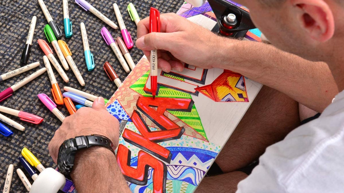 """A man uses a red marker to color in the word """"skate"""" across the bottom of a skateboard."""