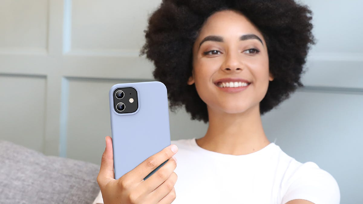 A smiling woman sits on a couch holding her iPhone with a light blue silicone case.