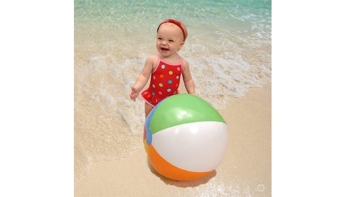 Little girl in red swimsuit, smiling with beach ball