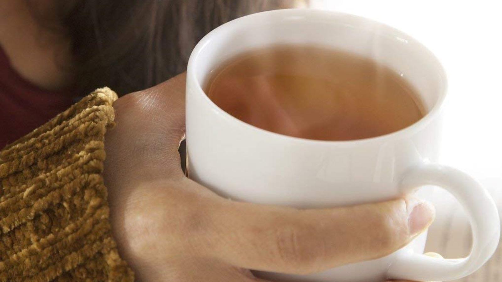 A woman holding a mug of rooibos tea.