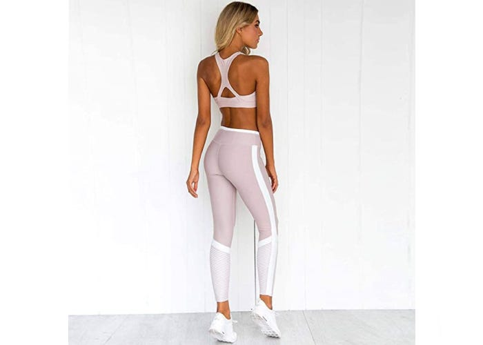A back view of a woman wearing matching set of light pink and white sports bra and leggings.