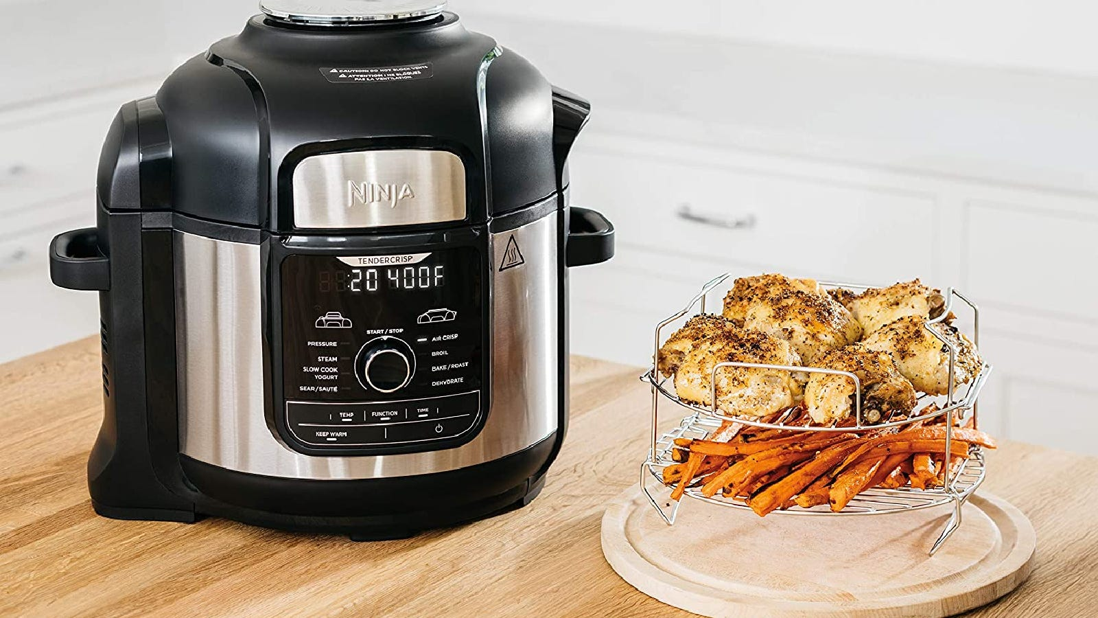 A Ninja Instant Pot with freshly cooked chicken and carrots along side of the appliance.