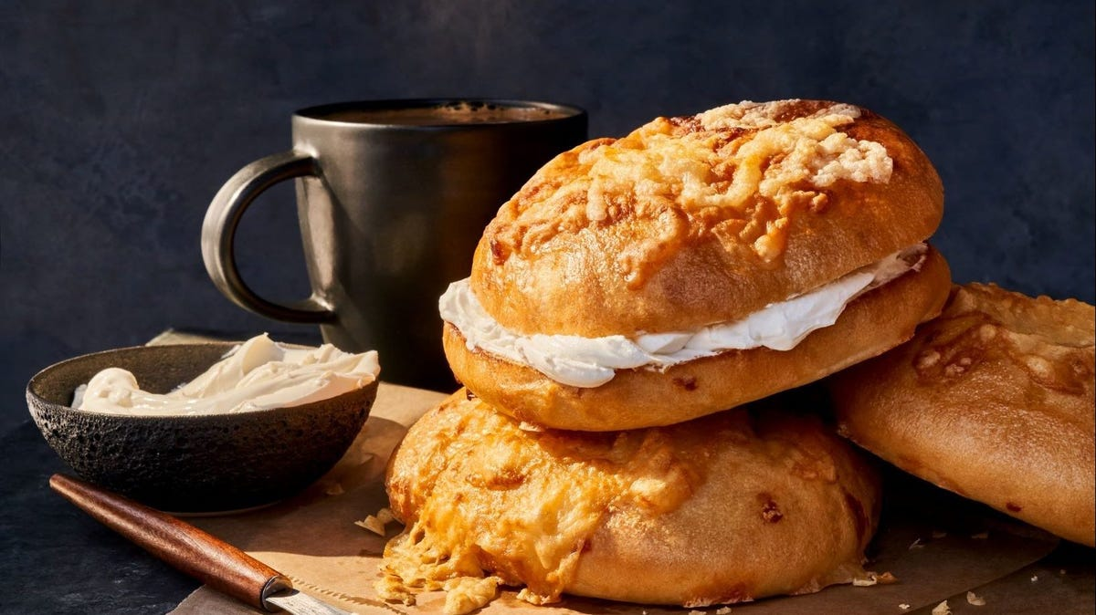 Three Panera bagels stuffed with cream cheese stacked on top of each other, next to a mug of coffee.