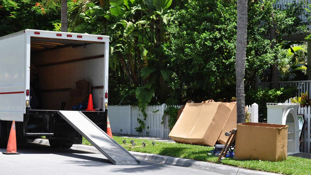 A charity truck collecting donations from the curb outside a home.