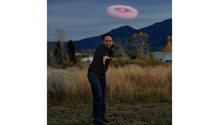 a man throwing an LED frisbee at dusk
