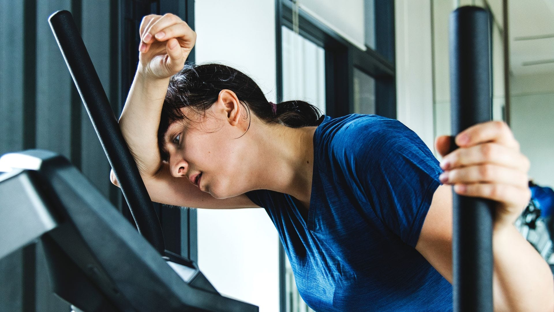 A woman who looks exhausted on an elliptical machine at a gym.