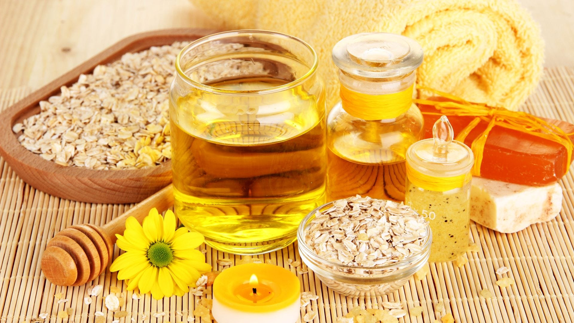 A bowl and wooden plate full of oatmeal surrounded by glass containers filled with honey.