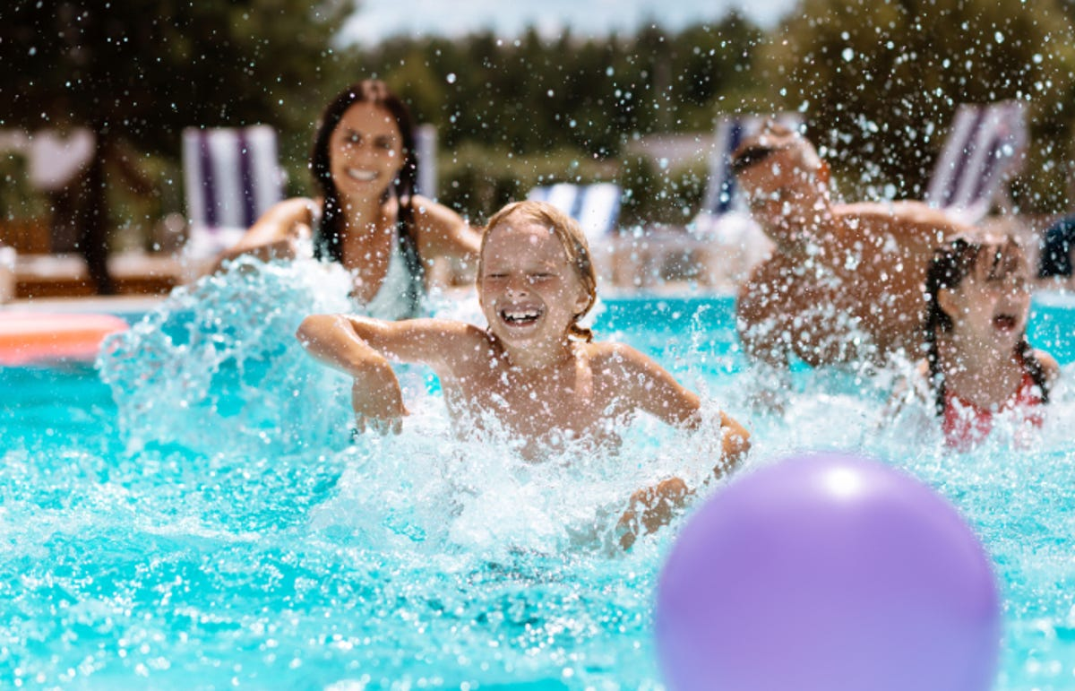 kids playing in the pool running after a purple ball on the surface of the water