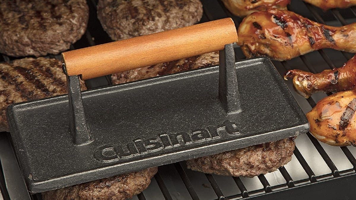 a rectangular Cuisinart grill press with a wooden handle on top of burgers on the grill