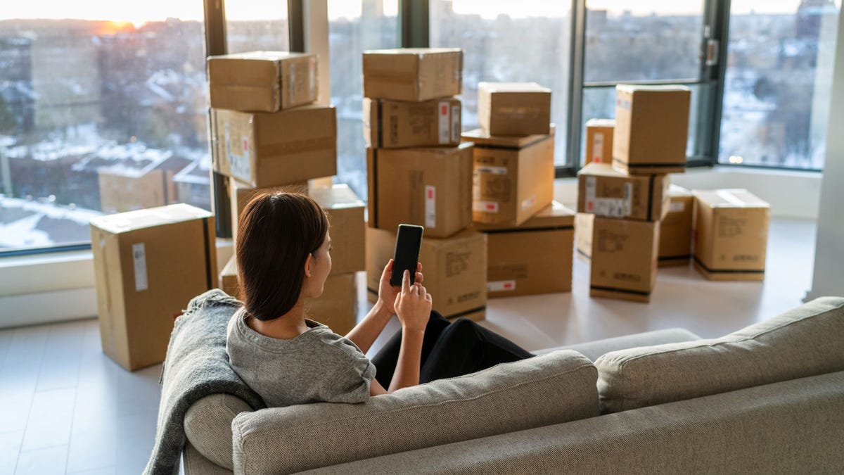 A woman surrounded by boxes looking for a moving company on her phone.
