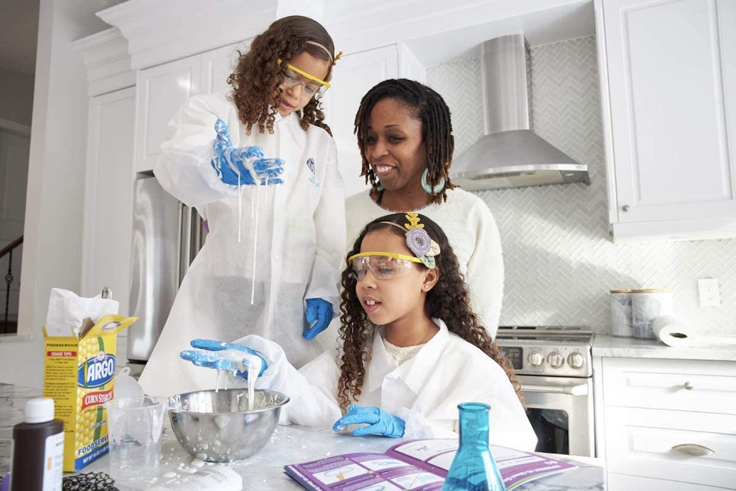 A woman and her two daughters wearing white lab coats and mixing goo in a bowl in a kitchen