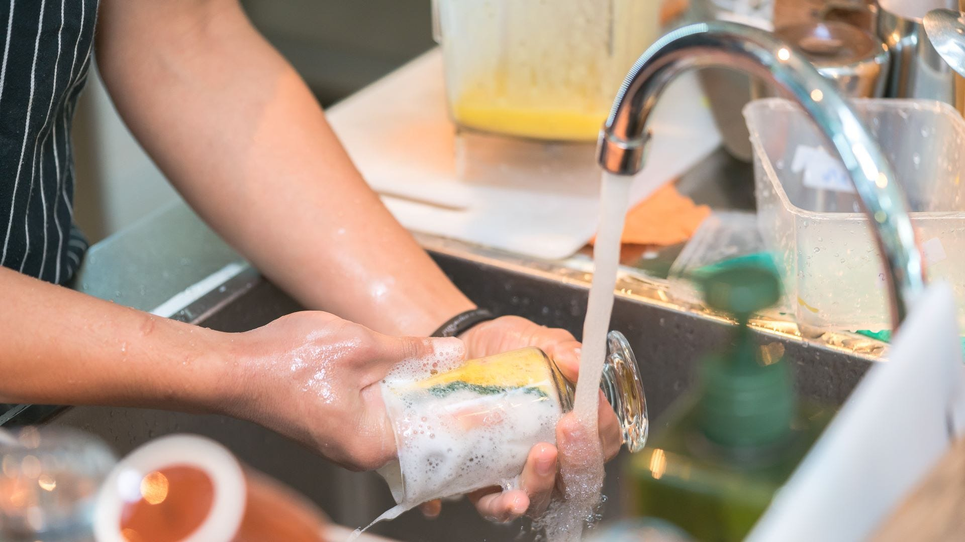 Someone rinsing a glass under a kitchen sink faucet.