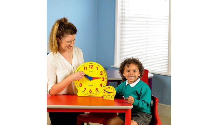 Student and teacher sitting together with super bright yellow teaching clocks