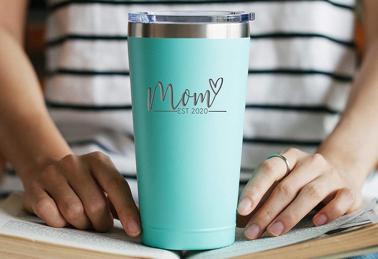 """A 16 oz. """"Mom"""" tumbler with lid sitting on an open book."""
