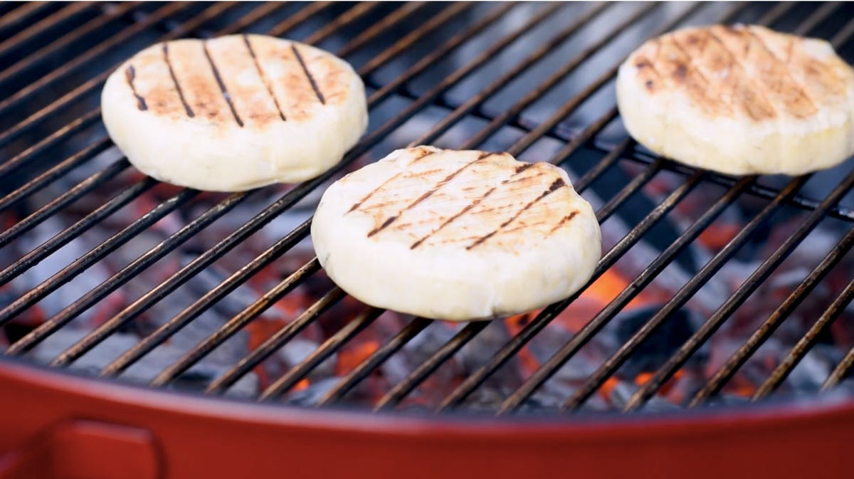 Three round slices of rougette bonfire cheese is placed on a grill.