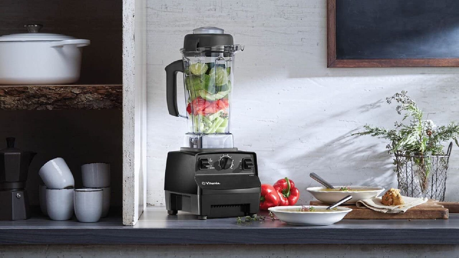A premium quality Vitamix blender on a counter filled with ingredients to make a homemade salsa.
