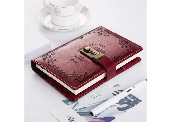 a leather journal with a three-digit lock code on the front with a teacup and a pen on the sides of it