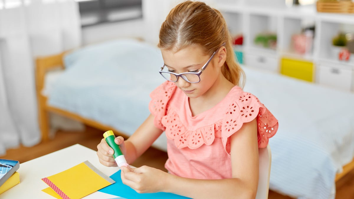 A young girl using a glue stick on colorful paper.
