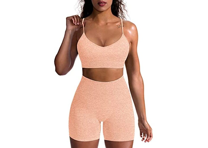 Model in matching peached colored, high-waisted workout shorts and sports bra.