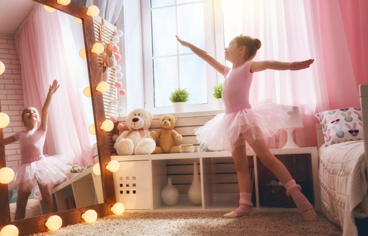 little girl in tutu and ballet shoes dances in front of her mirror