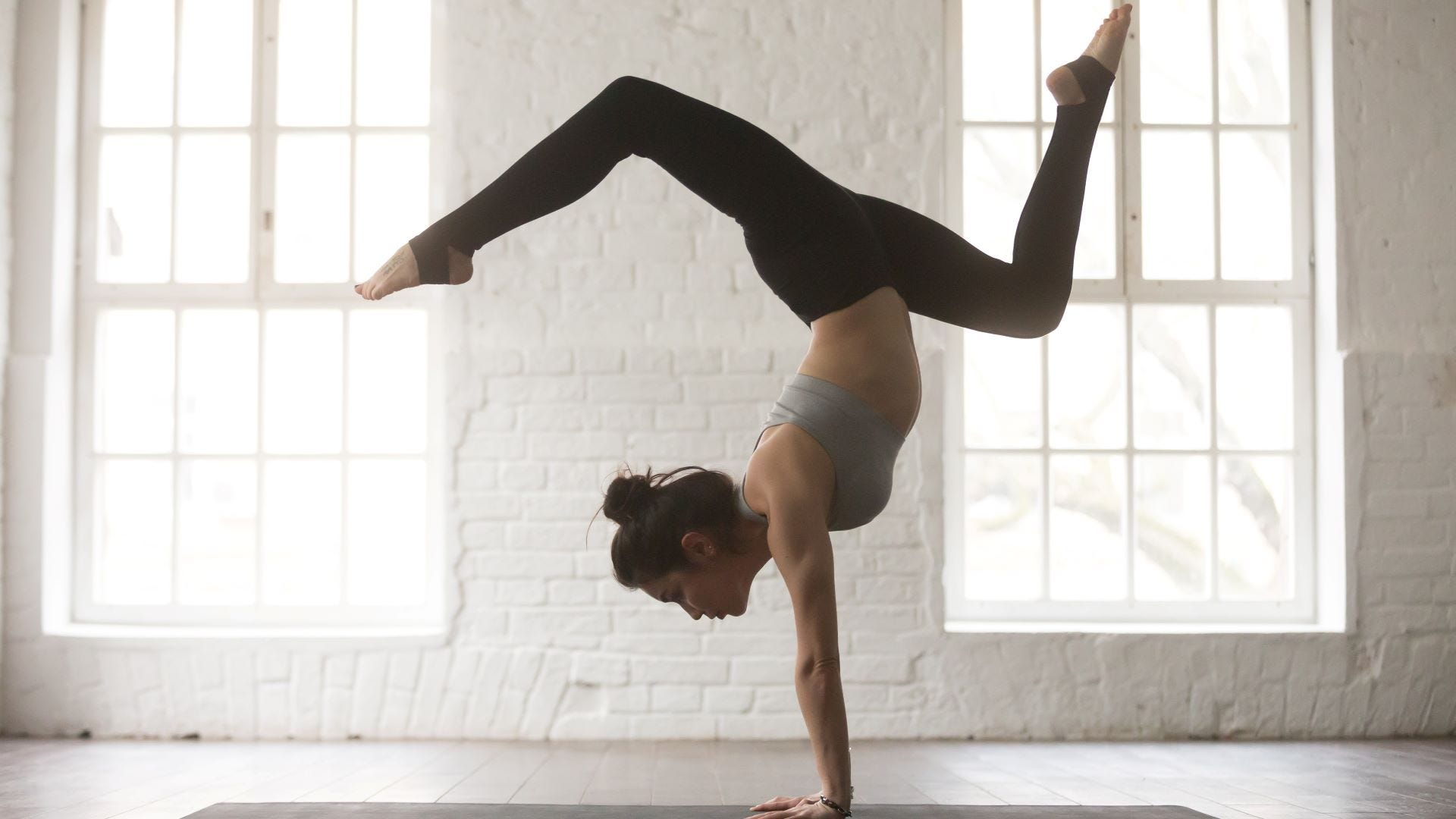A woman doing a yoga inversion pose in a studio.