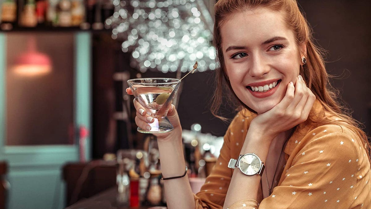 A young woman sits in a bar and holds a stemless martini glass.