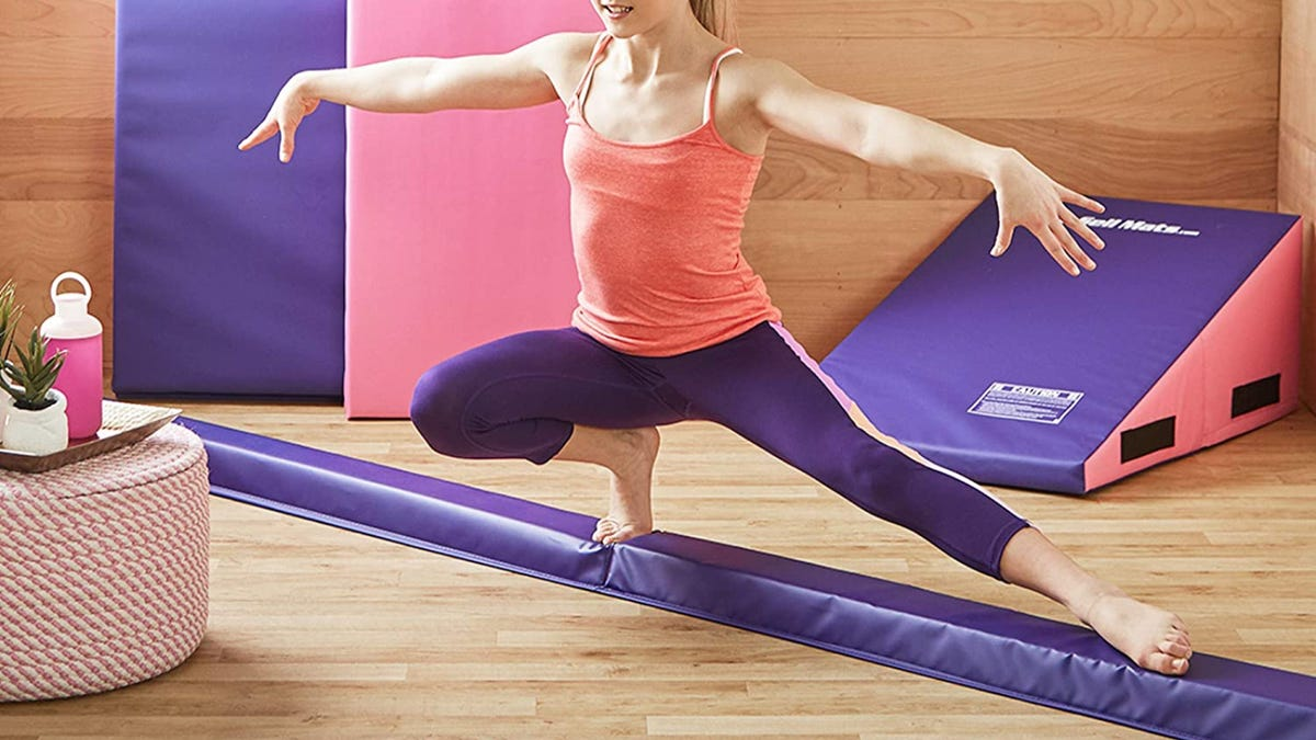 A woman wearing a pink tank top and purple leggings balances on a purple floor beam.